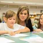 Two students sitting in library with talented educator